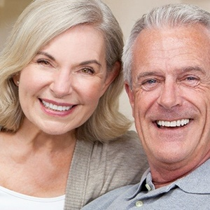 An older couple sitting on a couch and smiling after meeting with their dentist to learn about the cost of dental implants in Fayetteville
