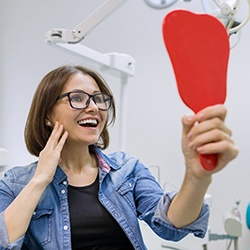 A middle-aged woman wearing glasses and looking at her new smile thanks to affordable dental implants