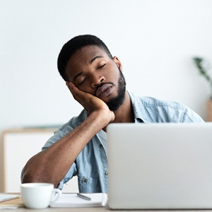 tired person falling asleep at laptop