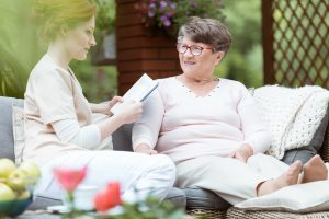 Senior woman and care giver sitting outdoors