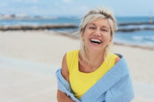 woman smiling with dental implants in summer